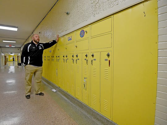 Lexington Junior High Principal Taylor Gerhardt shows how student's lockers are loose and hanging off the walls.