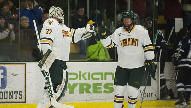 Catamounts defenseman Nick Luukko (25) and Catamounts goalie Brody Hoffman (37) celebrate a goal during a game earlier this season against New Hampshire.