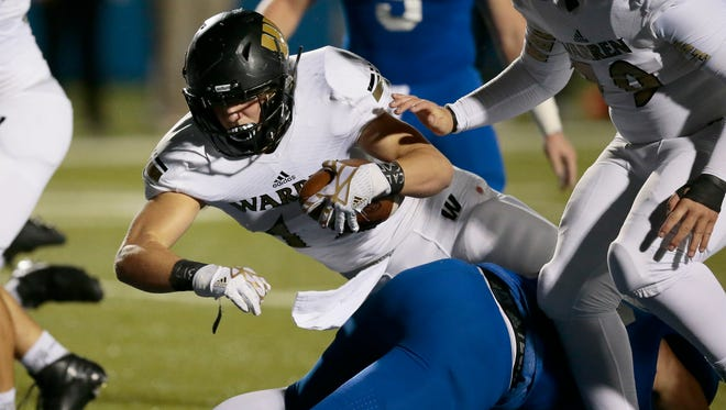 Warriors' Tristen Tonte keeps the ball for a touchdown run up the middle in the second quarter of a high school football game between the St. Xavier Bombers and the Warren Central Warriors at St. Xavier High School on Friday night in Cincinnati.