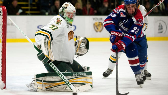 Vermont goalie Brody Hoffman (37) makes a stick save as UMass-Lowell forward Scott Wilson (23) looks on during the men's hockey game in January, 2013