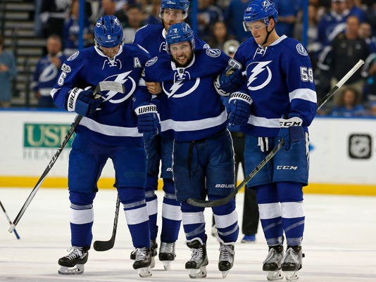 Tampa Bay Lightning's Tyler Johnson, center, is helped off the ice by Anton Stralman, left, of Sweden, and Jake Dotchin as Victor Hedman, of Sweden, follows during the second period of an NHL hockey game against the Minnesota Wild Thursday, March 9, 2017, in Tampa, Fla. (AP Photo/Mike Carlson)