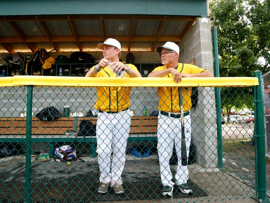 Ty Kurth (left) stands in the dugout with his father,