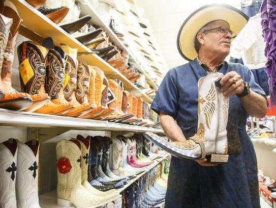 Rogelio Cabrera, shows off boots at his store, Tienda
