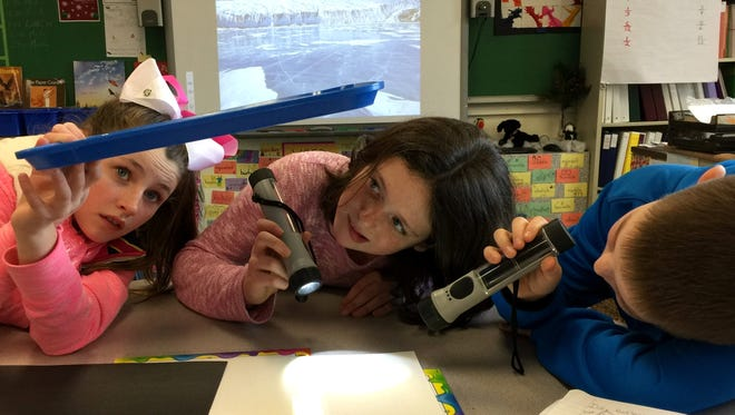 Cottage Lane students (Hannah, Olivia and Michael) experiment with reflective surfaces to understand why ice on Earth moderates our planet's climate.