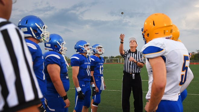 The referee does the coin toss before the game.