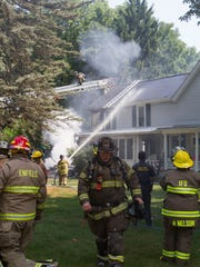 Firefighters work to extinguish a blaze Wednesday on Cayuga Street in Trumansburg. The fire destroyed a garage and killed two pets.