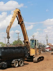 Crews work to unload a truck carrying metals Friday