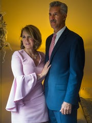 Linda Waugh wears a blush Milly bell sleeve shift dress and navy suede and sequin peep-toe Enzo Angiolini heels. Ted Waugh wears a Michael Kors Navy suit from Macy's; white Brooks Brother shirt; and brown Brownstone leather dress shoes.