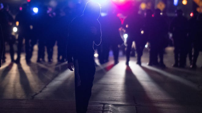 A man stands in the middle of S. Kansas Avenue on June 1 while Kansas Highway Patrol officers move in to disperse crowds.