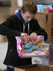 Volunteer Colton Flage with Boy Scout Troop 363 packs toys during the Salvation Army's Angel Tree toy distribution on Thursday morning.