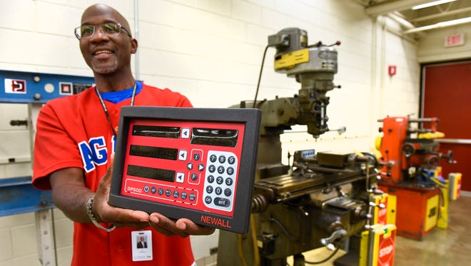 Apollo High School Principal Al Johnson shows a digital read out device Friday, Sept. 15, that will be installed on a milling machine in the industrial technology classroom to improve the machine's precision.