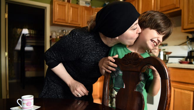 Ahmad Al Samakeh, 7, tries to wriggle away from his mother, Abeer Karkoutly, in the kitchen of their home in Paterson. Karkoutly and her husband, Khaled Al Samakeh, fled Syria with four of their children after being granted refugee status in the United States. Now, however, the family is struggling to repay nearly $5,000 in travel expenses.