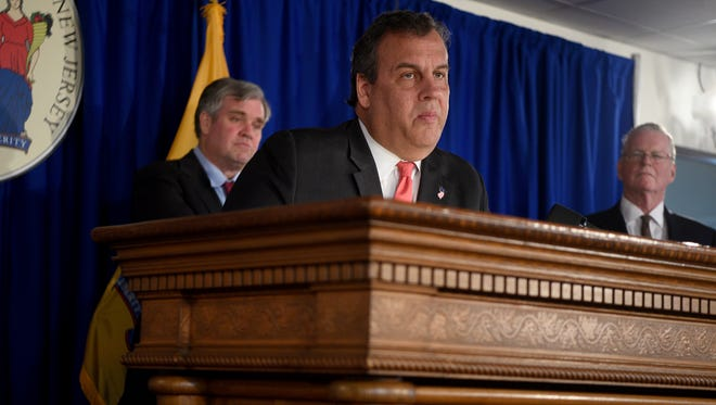 Gov. Chris Christie, with commission members Tom Byrne, left, and Thomas Healey, speaks at Wednesday's press conference in Trenton to announce the pension commission's final report.