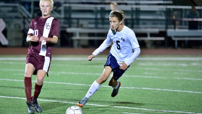Jason Freeman (5) dribbles the ball for Greencastle  against State College. Little Lions defeated the Blue Devils 1-0 in double OT in a PIAA Mid-Penn Conference playoff soccer match on Tuesday Oct. 17, 2017 at Kaley Field.
