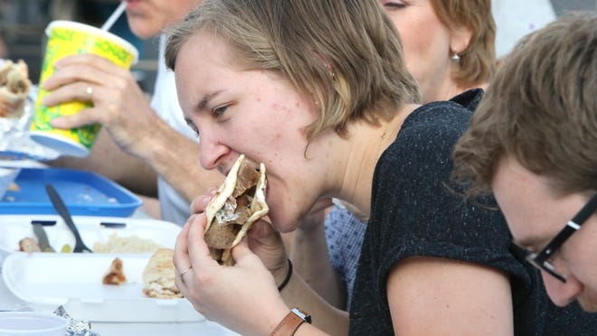 Samantha Harbert enjoys a gyro during last year's Canton Greek Fest at St. Haralambos Greek Orthodox Church in Canton. This year's event will be drive-thru service only July 16-18 at the church.