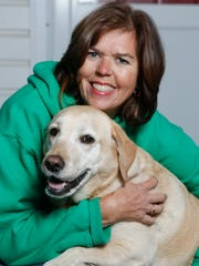 Julie Miller with Lacey, a 7-year-old yellow lab who won the therapy dog title in the Second Annual Animal Hero Awards.