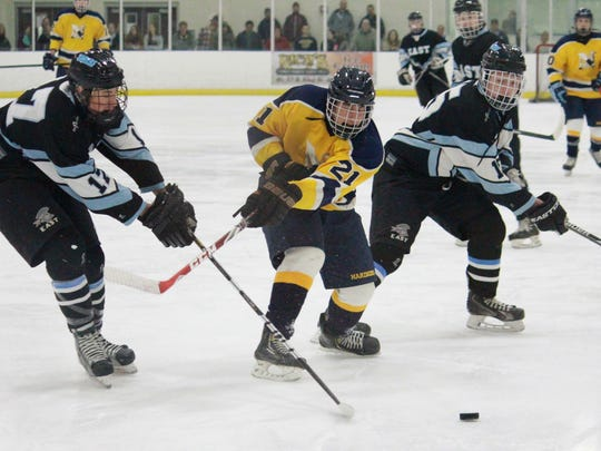 Colton Shan (21) battles for possession in the offensive zone in the 8-5 Mayor's Cup victory.