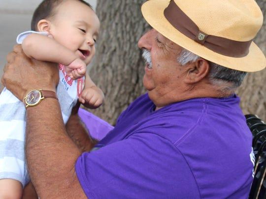 Jesus Hernandez gently swings his grandson, Crus, 6 months, under a Wildcat Country tree Saturday.
