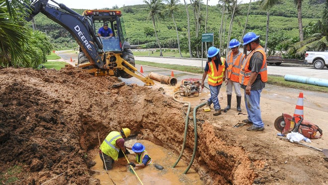 Guam Waterworks Authority employees in a hole measure the length for a replacement pipe needed to repair a 12-inch line water break under the roadway at Talofofo Bay on Monday, Aug. 17. Rick Cruz/Pacific Daily News/rmcruz@guampdn.com