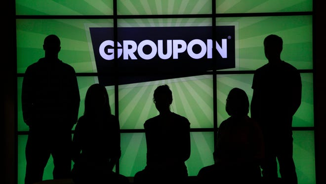 Employees at Groupon pose in silhouette by the company logo in the lobby of the online coupon company's Chicago offices.