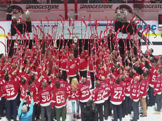 Current and former Red Wings raise their sticks for