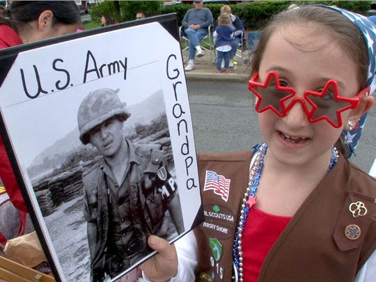 Troop 915 brownie Meadow Mirabello, 7, Howell, marches with a photo of her grandfather Vietnam veteran Robert Siebert along Main Street during the 44th Anuual Farmingdale Memorial Day Parade Monday, May 29, 2017.
