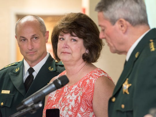 Jill Heddy listens as Sheriff David Morgan, right,