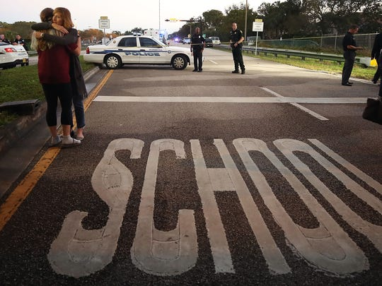 PARKLAND, FL - FEBRUARY 15: Kristi Gilroy (R), hugs a young woman at a police check point near the Marjory Stoneman Douglas High School where 17 people were killed by a gunman yesterday, on February 15, 2018 in Parkland, Florida. Police arrested the suspect after a short manhunt, and have identified him as 19-year-old former student Nikolas Cruz.  (Photo by Mark Wilson/Getty Images) *** BESTPIX ***