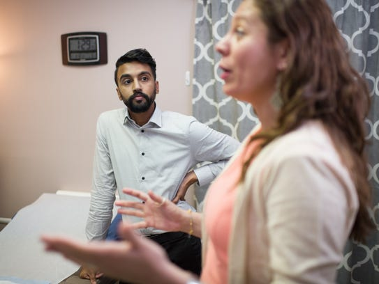 Bhavik Kumar, M.D., looks on as Andrea Ferrigno, corporate