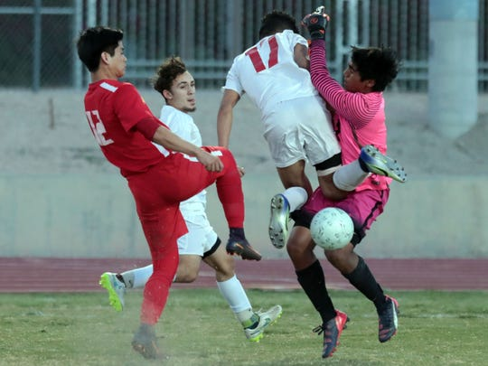 Palm Desert's Jhonatan Urbina collides with the Woodbridge goalkeeper in the first half of a playoff game on Friday, February 16, 2018 in Palm Desert.