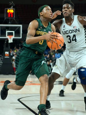 Michigan State guard Cassius Winston (5) drives past Connecticut forward David Onuorah (34) for a basket during the second half of MSU's 77-57 win in the Phil Knight Invitational tournament on Friday, Nov. 24, 2017, in Portland, Ore.