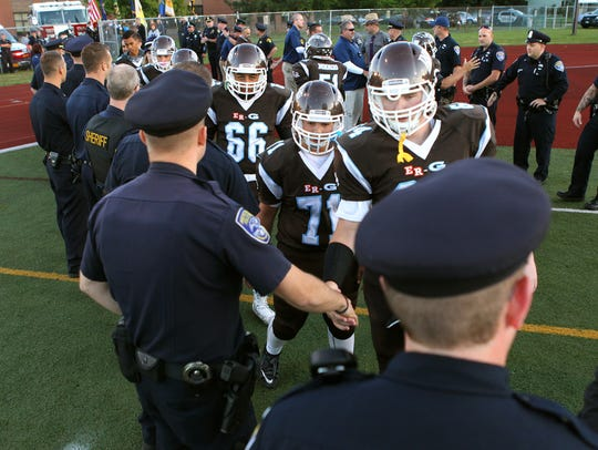 East Rochester/Gananda players shake hands with law enforcement officers prior to a game in 2014 against Wayne during a ceremony in honor of fallen Rochester Police Department Officer Daryl Pierson.