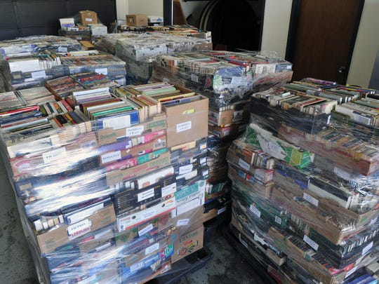 Pallets of books wait to be displayed on tables for