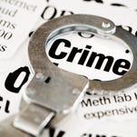 Handcuff rests on crime headline in pile of newspaper cuttings