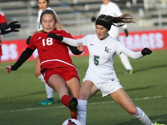 Indian Hill's Ellie Podojil (18) battles Lake Catholic's Kennedy Newhard during their 2-0 win in the DII State Soccer Final, Friday, Nov. 10,2017.