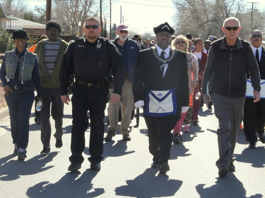 Alamogordo Police Chief Daron Syling, Prince Hall Masonic Hall No. 11 member Everette Brown and Mayor Richard Boss walk down Washington Avenue together during the Martin Luther King March Monday.