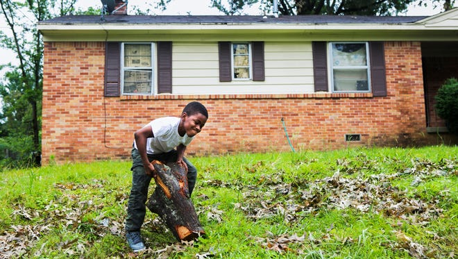 June 4, 2017 - King Garvin, 10, grimmaces as he lifts a stump to add to a pile of debris he's discarded in front of his yard on Coventry Dr. in Frayser Sunday afternoon. Crews from the City of Memphis worked to remove fallen trees and debris from the area as a result of last week's storm that left thousands of people without power. MLGW's outage map shows 6,500 customers are still without power as of noon Sunday.