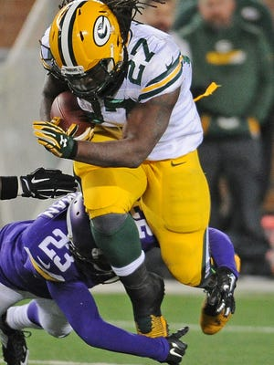 Green Bay Packers running back Eddie Lacy (27) jumps through a hold as Minnesota Vikings cornerback Terence Newman (23) dives in for the tackle at TCF Bank Stadium in Minneapolis November 22, 2015.
