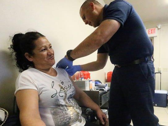 Yolanda Palomares of El Paso gets a flu vaccination from El Paso Fire Department paramedic Lt. Edward Montoya.