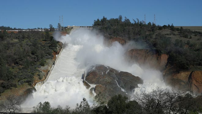"In this Saturday, Feb. 11, 2017, water flows down Oroville Dam's main spillway near Oroville, Calif. Officials ordered residents near the Oroville Dam to evacuate the area Sunday, Feb. 12, saying a ""hazardous situation is developing"" after an emergency spillway severely eroded."
