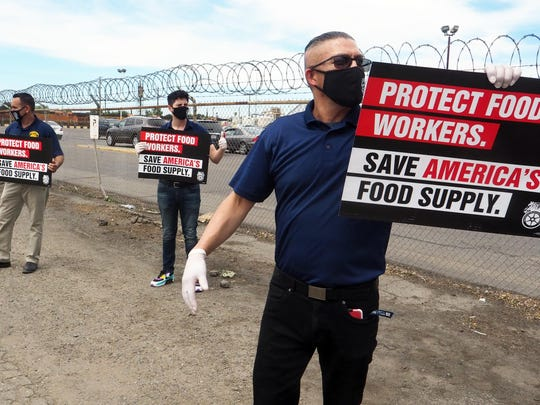 Teamsters Local 856 Albert Zamora, left, Mauricio Ocegueda and Manuel Rodriguez hold pickets signs near the entrance to Diamond Foods in Stockton, Calif. this summer.