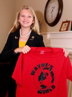 """Emma Wayne, who won state and national Beta Club titles during recent conventions, holds up a shirt that was used during her """"Wayne's World"""" themed campaign."""