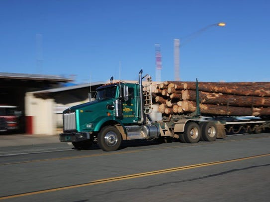 A logging truck heads along Main Street in downtown