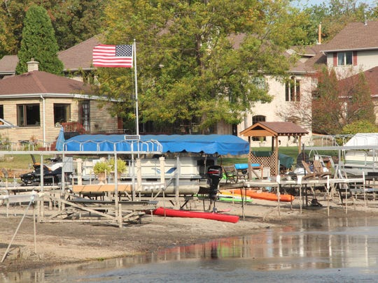 Piers and boats are high and dry on a portion of Little Muskego Lake during a drawdown to treat starry stonewort, an invasive aquatic species.