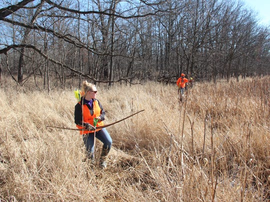 Hanna Meyer of Winchester, Wis., left, and John Laidlaw of Plover, Wis. push a grassy edge of a pond during a traditional archery hunt for ring-necked pheasants at a private club in Pleasant Prairie, Wis.