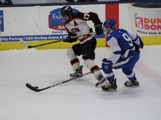 Brighton senior Adam Conquest (17) and DCC junior Caleb Saeter go after a lose puck.