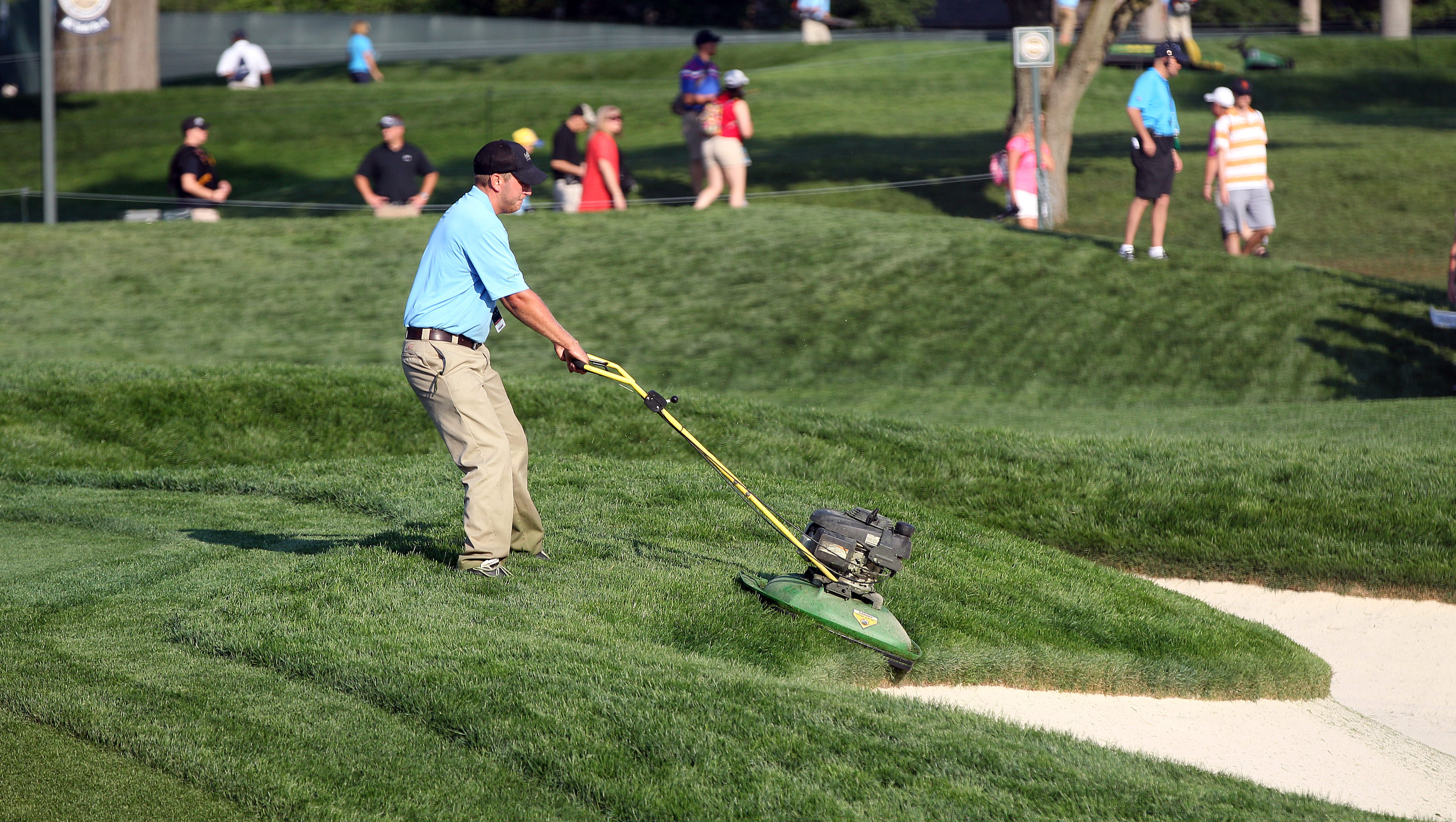 A member of the grounds crew cuts the rough along the 6th hole.