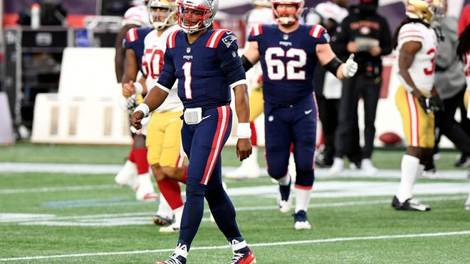 Patriots quarterback Cam Newton (front) walks off of the field after throwing an intercepting against the 49ers during the first half at Gillette Stadium on Sunday.