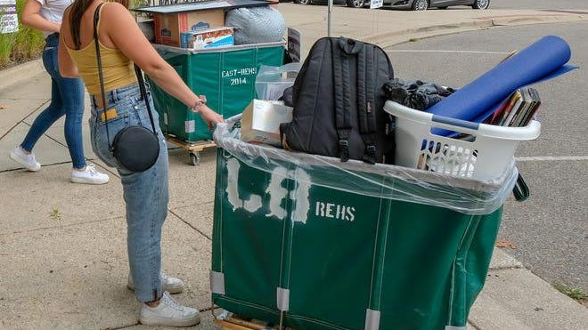 Incoming MSU freshman, Sarah Scott, from Grosse Pte. Woods, center, holds on to one cart as her sister Alice, left, and their mom Nicole, load up another at North Case Hall Sunday, Aug. 30, 2020. Michigan State limited the number of students moving into dormitories to 2,000 this year due to the COVID-19 pandemic.