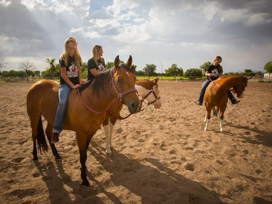 Members of the NMSU equestrian team, Pearl Aebly, left, Haley Newkirk and Hallie Padilla ride horses at the university's Equestrian Center, Friday, July 15, 2016.